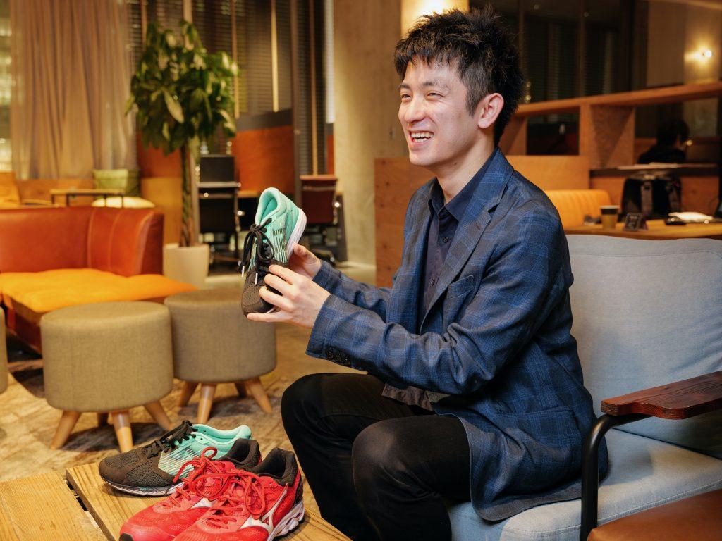 石田さんが笑顔で靴を持っている