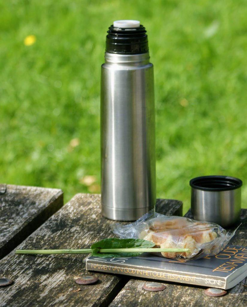 ステンレス製の魔法瓶がテーブルに置いてある。自然のなかで本が隣にある。
