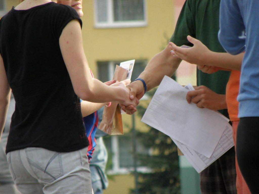手をつなぐひとたち。書類を持っている。