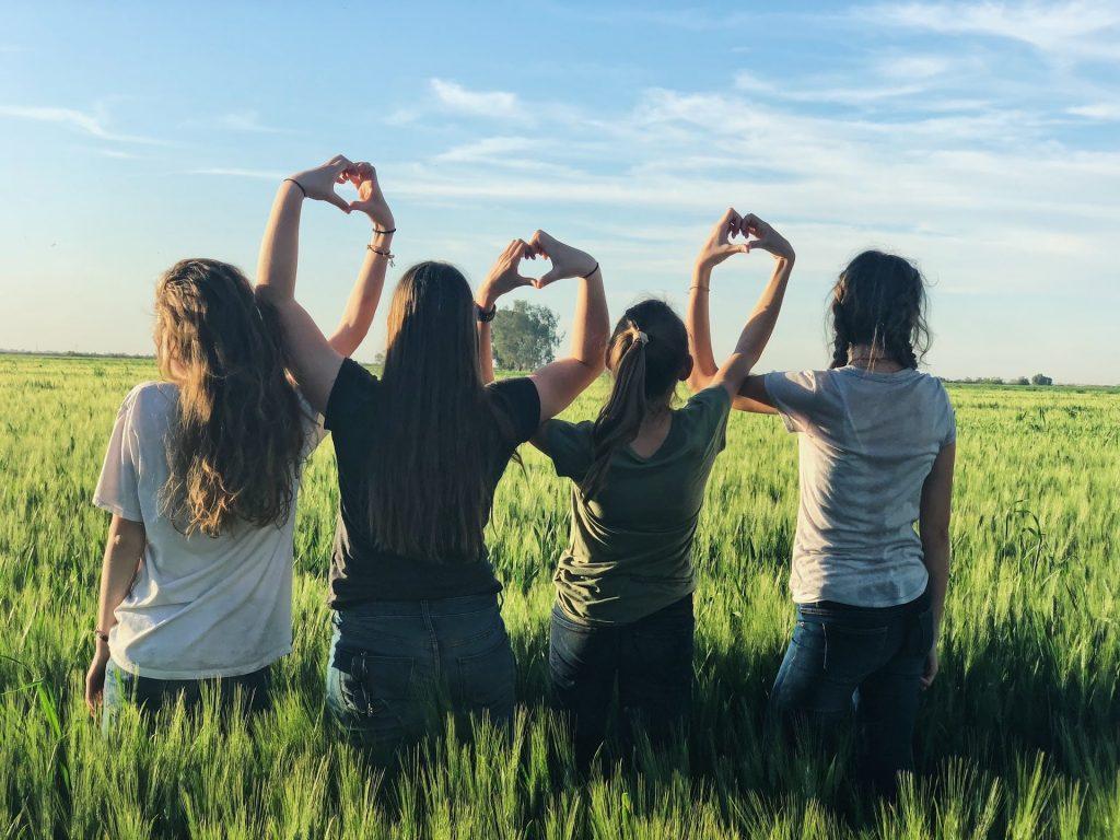 お互いの手でハートを作る4人の少女